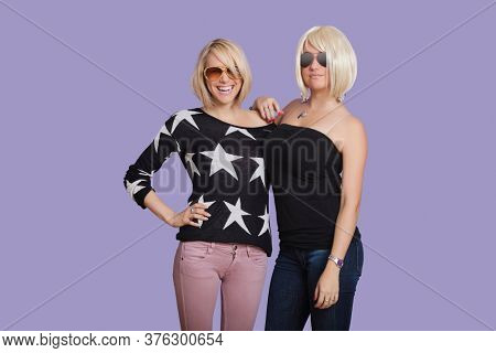 Portrait of two beautiful multi ethnic women smiling over purple background