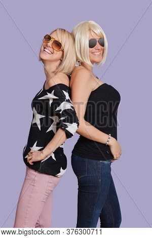 Portrait of two beautiful multi ethnic women back to back over purple background
