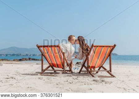 Romantic Holiday Travel. Portrait Of Happy Young Couple Hugging Near With Deck Chairs In Luxury Beac
