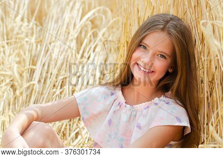 Portrait Of Smiling Cute Little Girl Child Sitting On Field Of Wheat Outdoor