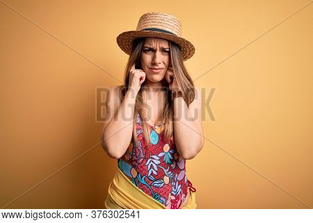 Young beautiful blonde woman wearing swimsuit and summer hat over yellow background covering ears with fingers with annoyed expression for the noise of loud music. Deaf concept.