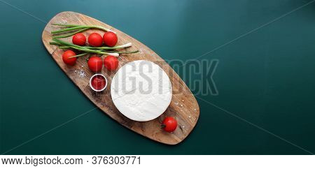 Homemade Goats Milk Cheese, Small Tomatoes On A Branch, Red Sauce On A Wooden Board On A Dark Green