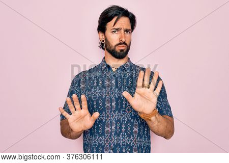 Young handsome hispanic bohemian man wearing hippie style over pink background Moving away hands palms showing refusal and denial with afraid and disgusting expression. Stop and forbidden.