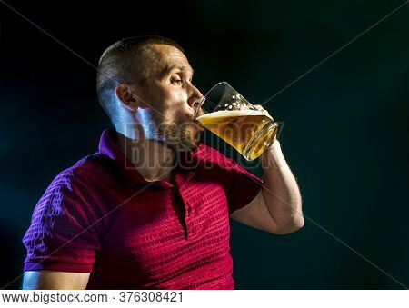 Man Enjoys Drinking Beer From A Mug On A Dark Green Background