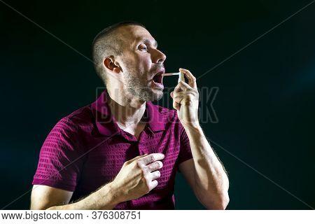 A Man Sprays Medicinal Spray For Sore Throat