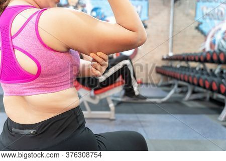 Woman Holding Hand Excessive Fat Arm At Gym. Woman Pinching Arm Fat Flabby Skin. Weight Loss, Slim B