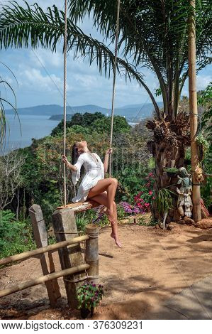 Charming Girl In Stylish White Dress Swinging On Hanging Swing In A Tropical Jungle. Concept Of Beau