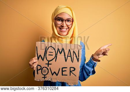 Beautiful woman with curly hair wearing muslim hijab asking for women rights holding banner very happy pointing with hand and finger to the side