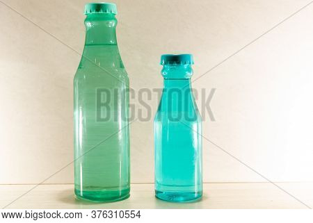 Colored Glass Bottles With Natural Water On Light And Illuminated Background