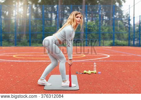 Young Blond Beautiful Slim Fit Girl In Gray Sportswear Doing Squats And Stretching Exercise With Red