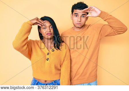 Beautiful latin young couple wearing casual clothes together worried and stressed about a problem with hand on forehead, nervous and anxious for crisis
