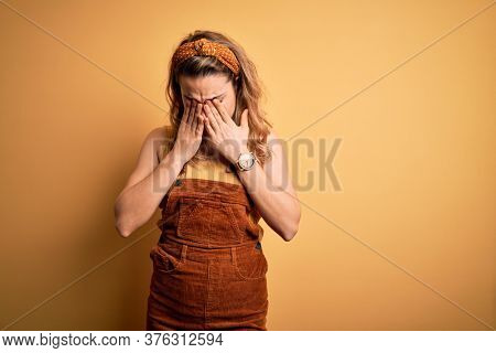 Young beautiful blonde woman wearing overalls and diadem standing over yellow background rubbing eyes for fatigue and headache, sleepy and tired expression. Vision problem