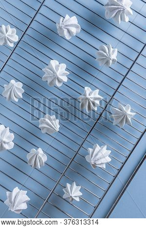 Few Delicate White Meringue Cookies Cooling Down On Steel Metal Grate. Light Blue Paper Background.