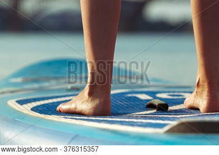 Close Up Legs. Young Attractive Woman Standing On Paddle Board, Sup. Active Life, Sport, Leisure Act