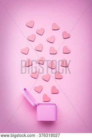 Pink Round Metal Gift Box With Small Wooden Hearts On A Delicate Pink Background.