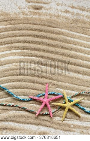Starfish And Colored Ropes On A Background Of Wavy Sand. Marine Cruise Theme. Top View With Place Fo