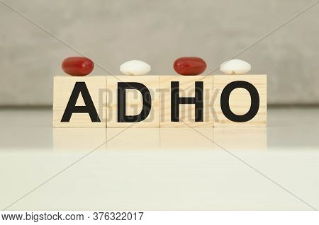 The Text Adho Is Written On Wooden Cubes With Tablets On Cubes