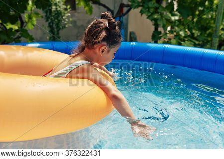 Side View Of A Child In Colorful Swimsuit Relaxing On An Big Inflatable Orange Ring Floating In A Po