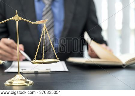 Scales Of Justice Standing In Front Of The Male Lawyer Is Providing Service To Consult Business Disp