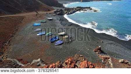 Volcanic  Coastline Rocks And Waves At El Golfo Lanzarote Spain With Boats On Beach.