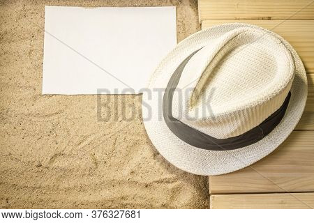 Shot To A Few Wooden Planks, Sand, A Few Summer Clothing Articles And A White Plain Piece Of Paper