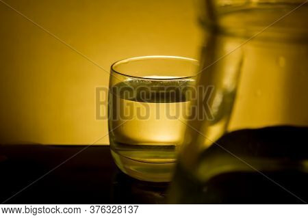 Elegant Shot Of A  Glass Of Water And A Pitcher On A Dark Background