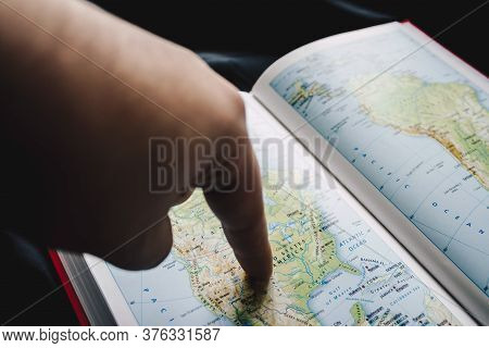 United States In Atlas. Man's Finger Shows Usa's Borders.