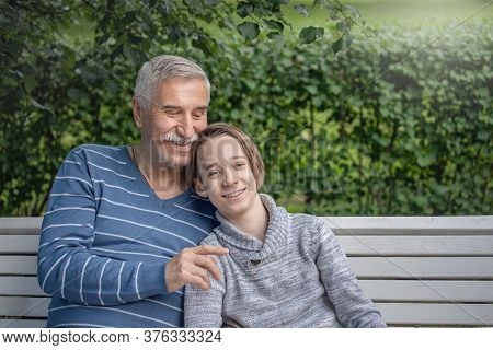 Portrait Of Grandfather And Grandson, A Boy And An Elderly Man Are Sitting In A Park On A Bench, Hug