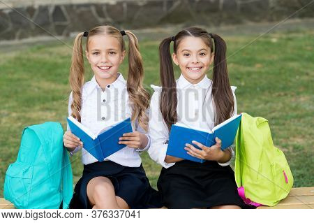 Reading Is The Key. Happy Children Read Books On Bench. Little Girls Enjoy Reading Outdoors. Home Re