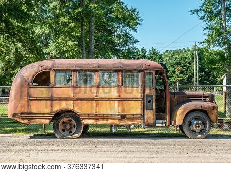 An Old Rusted School Bus With Broken Glass Windows And Flat Tires Sits Neglected Outdoors Side View