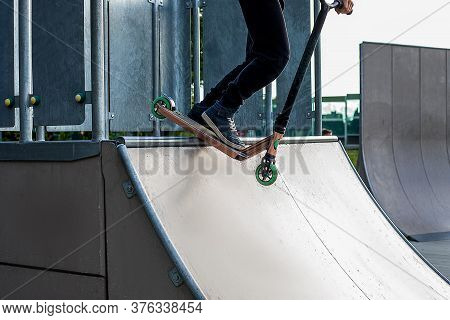 Teenager Boy Rides On Kick Scooter In Outdoor Skatepark. Summer Extreme Sports Outside. Feet Of Male