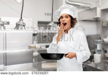 cooking, culinary and people concept - surprised female chef in toque with frying pan over restaurant kitchen background