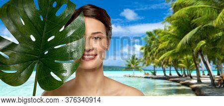 beauty, bodycare and people concept - beautiful young woman with green monstera leaf over tropical beach background in french polynesia