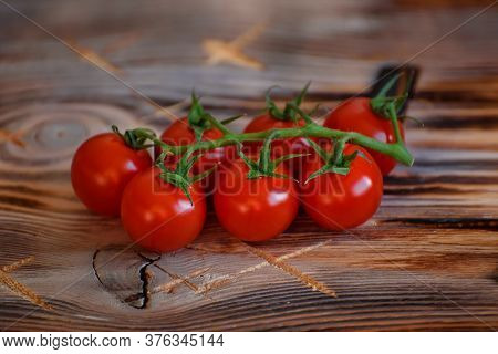 Sprig Of Ripe Fresh Cherry Tomatoes On The Old Brown Rustic Wooden Table. Ingridient For Vegetable S