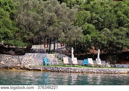 Private Beaches On Mediterranean Sea. Chairs, Deck Chairs, Sun Loungers And Parasols Waiting For Tou