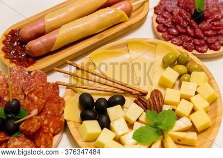 Antipasto Platter Assorted Sliced Cheeses, Sausages, Salami With Olives And Crackers On Wooden Plate