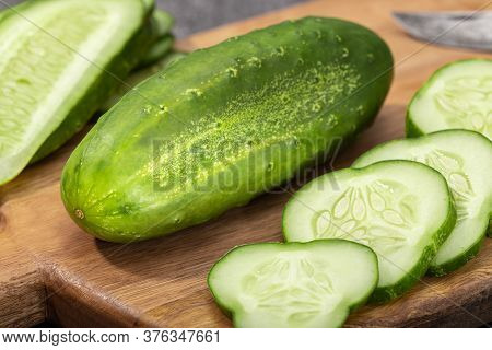 Organic Cucumber And Slices On Wooden Cutting Board. Cucumis Sativus