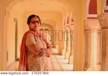 Happy Looking Senior Indian Lady Wearing Traditional Suit Posing In The Corridor Of Jaipur's City Pa