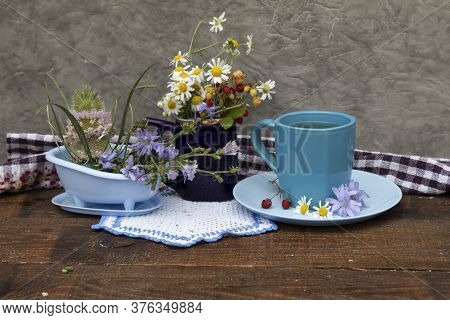 On The Table Is A Bouquet Of Daisies And Wild Strawberries, A Cup Of Tea, On A Saucer Lies Wild Stra