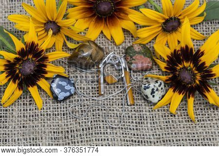 Close-up. In The Frame Of Yellow Flowers Lie Semiprecious Stones - The Tiger's Eye, Unakit, Snow Obs