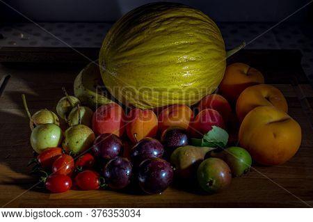 Frutas Frescas De Estación Sobre Mesa De Madera Con Melon, Peras, Tomates, Duraznos, Ciruelas, Damas