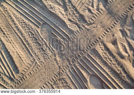 Tracks In Sand. Part Of Prints And Tracks Of Tire, Foot, Feet, Sun Sea Slippers In Beach Sand. Textu