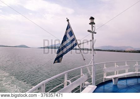 Close Up Of Blue And White Greek Flag On Flagpole Flying In Wind. Torn Greek National Flag Waving On