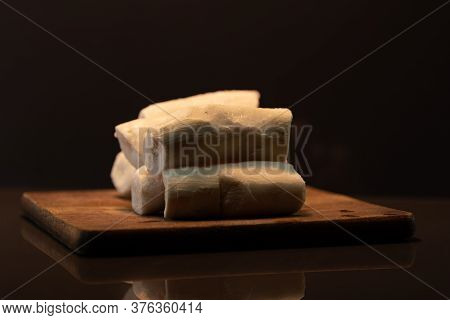 Edible Manioc Root (manihot Esculenta), Peeled And Frozen On Neutral Background