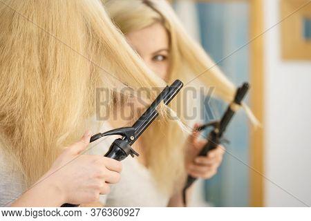 Woman Preparing Her Blonde Hair, Using Curling Pin In Home Bathroom. Hairdo Curler Creating Hairstyl