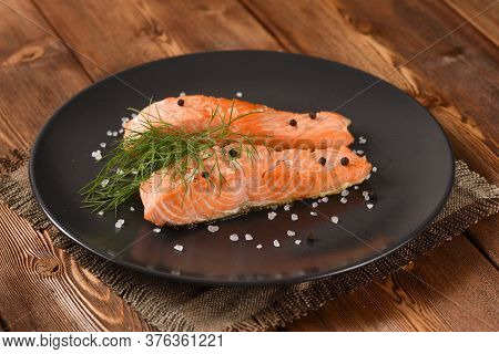 Fried Salmon Fillet With Fennel On The Black Plate.