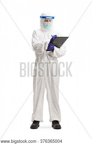 Full length portrait of a man in a hazmat suit writin a document isolated on white background