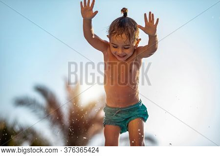 Cheerful Child with Pleasure Having Fun Outdoors. Little Boy Jumping into the Pool. Having fun in Aqua Park. Enjoying Active Summer Holidays.