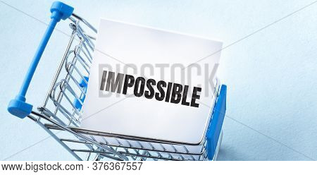 Shopping Cart And Text Impossible On White Paper Note List. Shopping List Concept On Blue Background