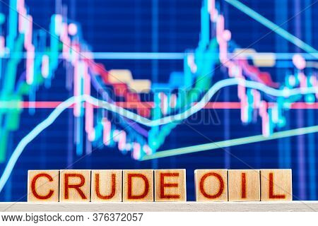 Crude Oil Index Concept. Wooden Blocks With The Inscription Crude Oil With A Chart On The Background